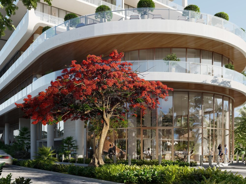 Front entrance of Mr. C Residences in Miami. Shrubs and maple tree in front of condo complex lobby with tall windows.