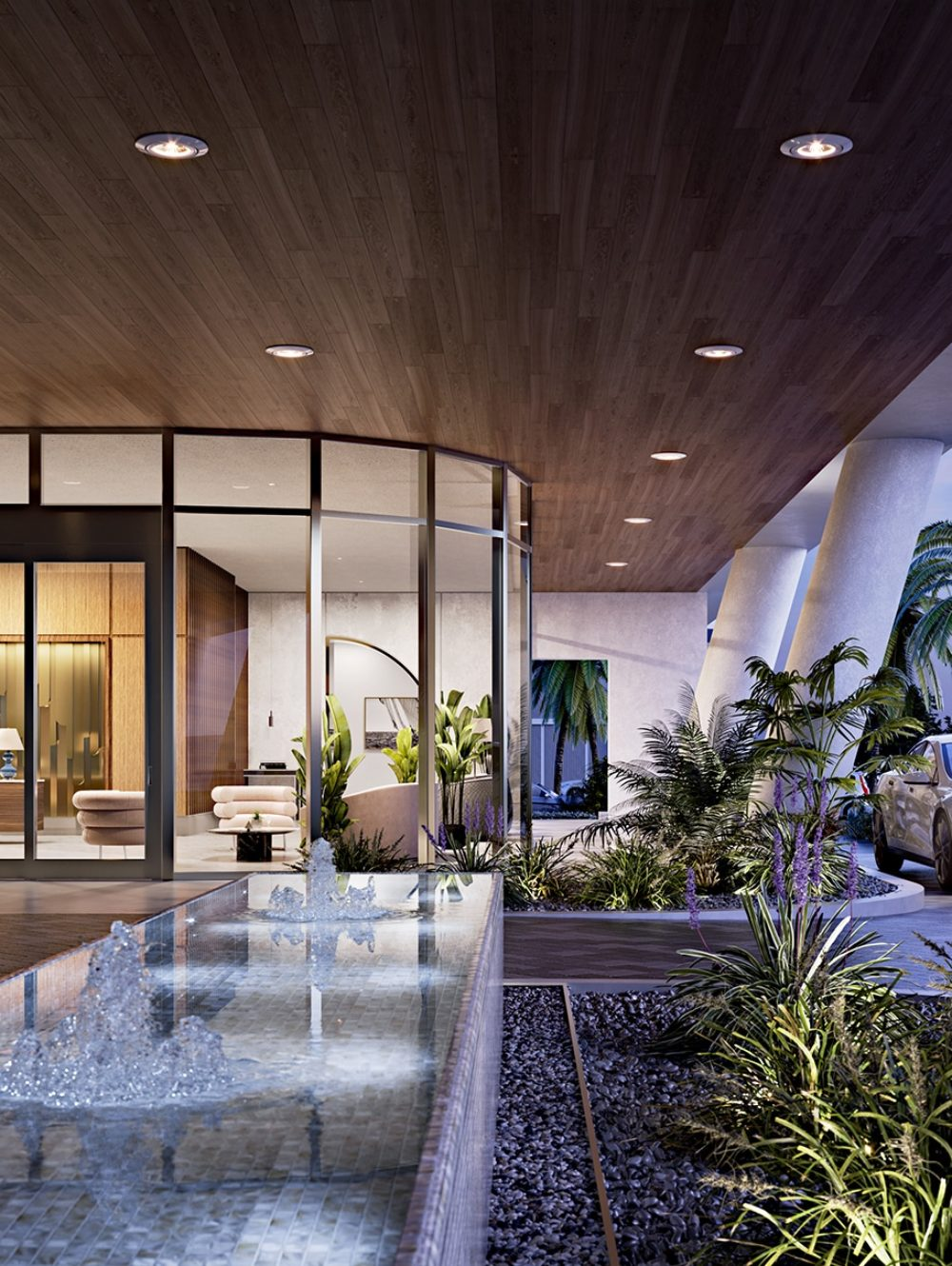 Front entrance and driveway at Mr. C Residences in Miami. Water fountain and ferns near floor-to-ceiling windows of lobby.