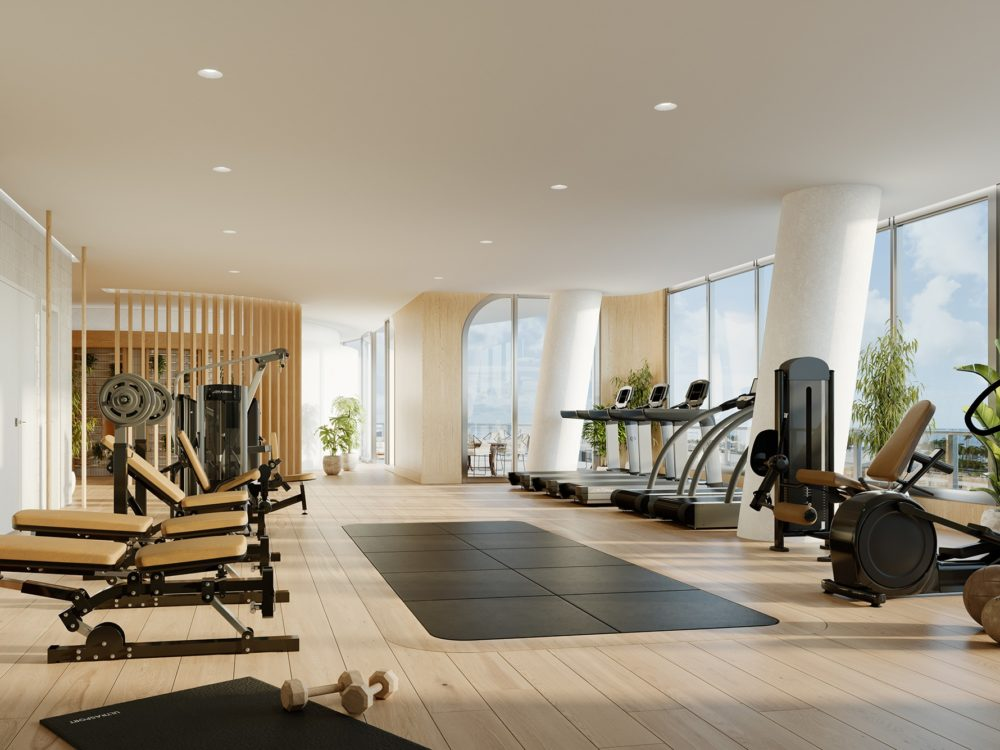 Gym at Mr. C Residences in Miami. Workout benches line a mirrored wall and cardio machines line floor-to-ceiling windows.