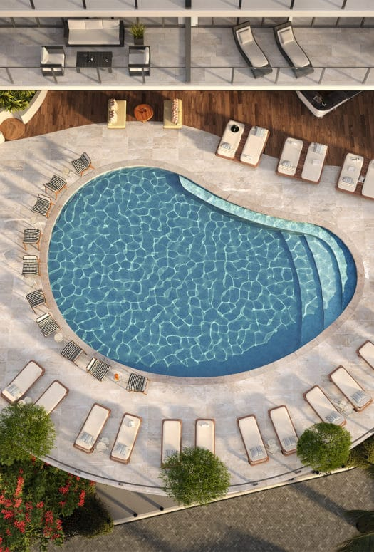 Aerial view of outdoor pool at Mr. C Residences in Miami. Pool at condo complex bordered by lounge chairs and trees.