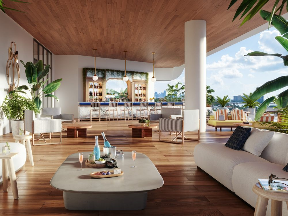 Pool side lounge at Mr. C Residences in Miami. White couches with bar in the background with stools and pool to the right.