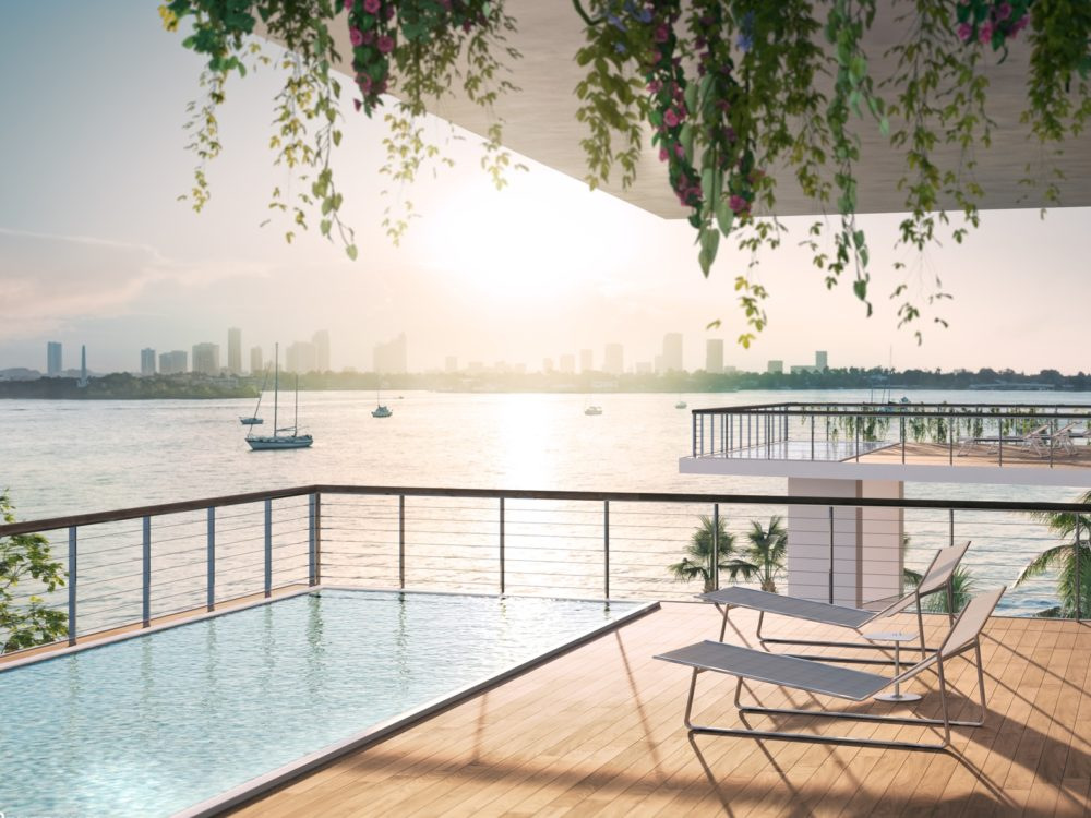 Luxury condo terrace at Monad Terrace in Miami. Wood terrace with deck furniture, glass railings and views of Biscayne Bay.