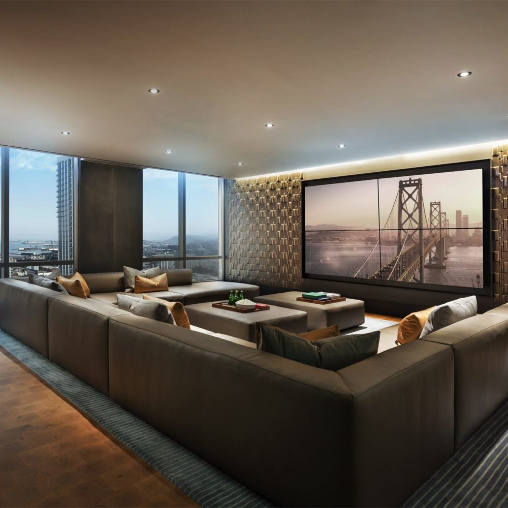 Media room and lounge at The Avery luxury condominiums in SF. Big screen TV with a large couches and dimmed lighting.
