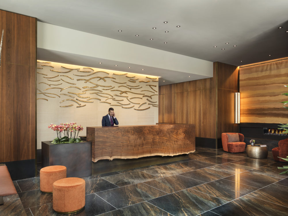 Lobby at The Avery condos in San Francisco. Natural wood walls, dark marble floors, seating and a front desk with concierge.