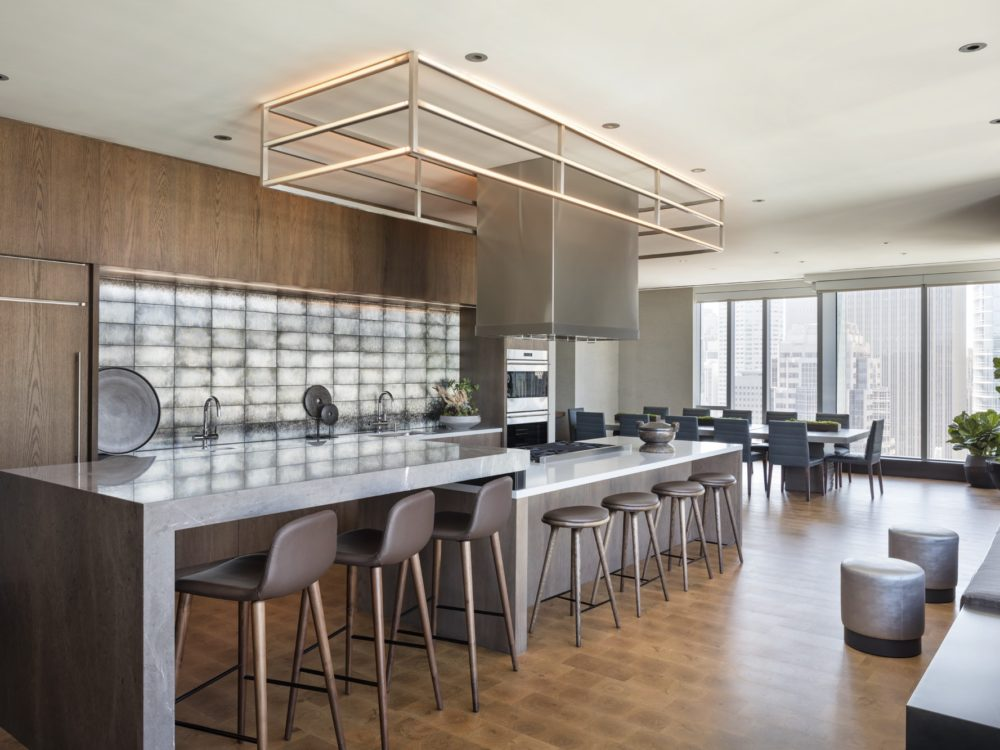 Demo kitchen for The Avery condos in SF. Long, two-tiered marble countertop with bar seating and free hanging range hood.