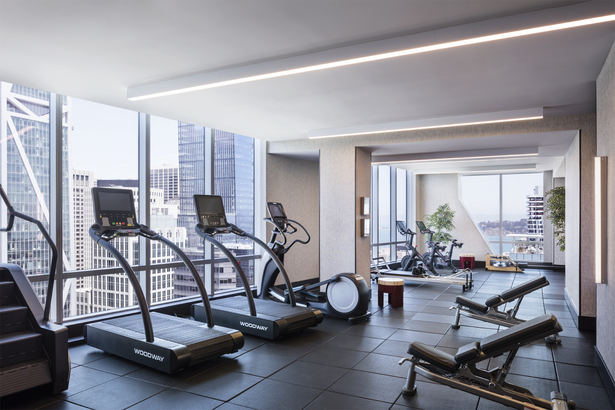 Gym at The Avery luxury condos in San Francisco. Oversized windows lined with treadmills & ellipticals providing city views.