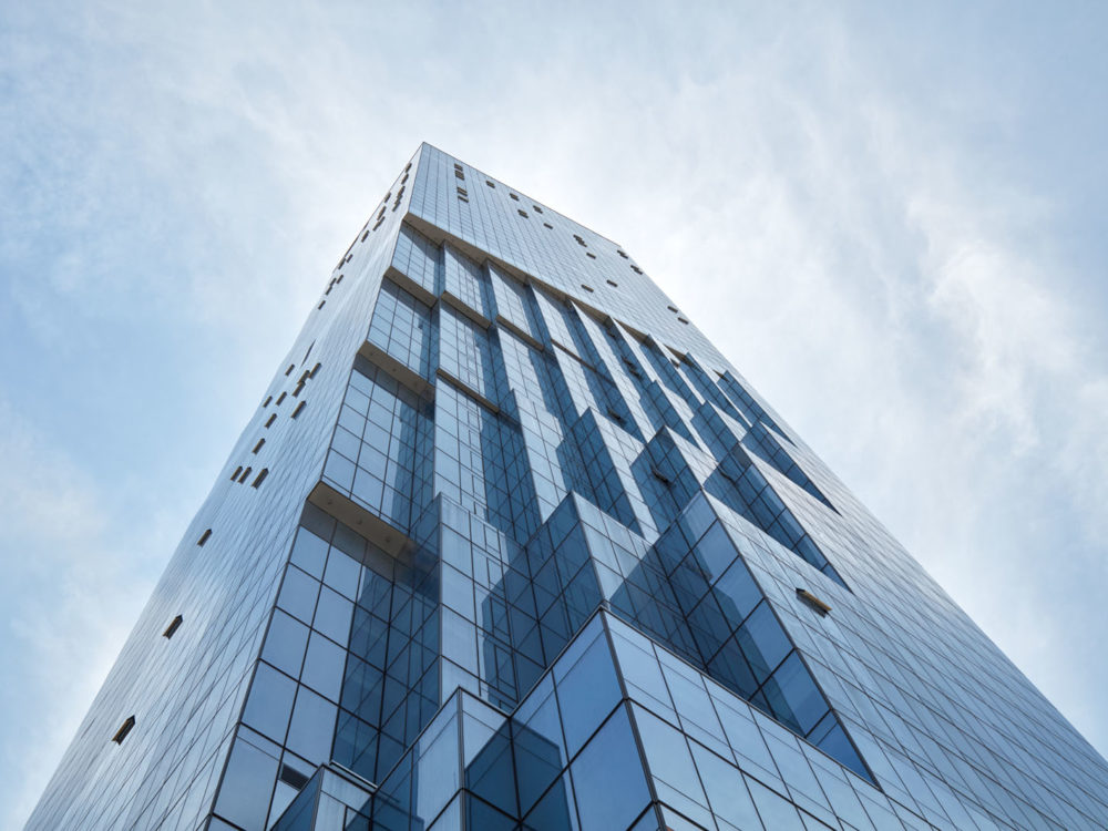 Exterior view of The Avery luxury condominiums in San Francisco. Lookup up at the glass tower into white clouds & blue skies.