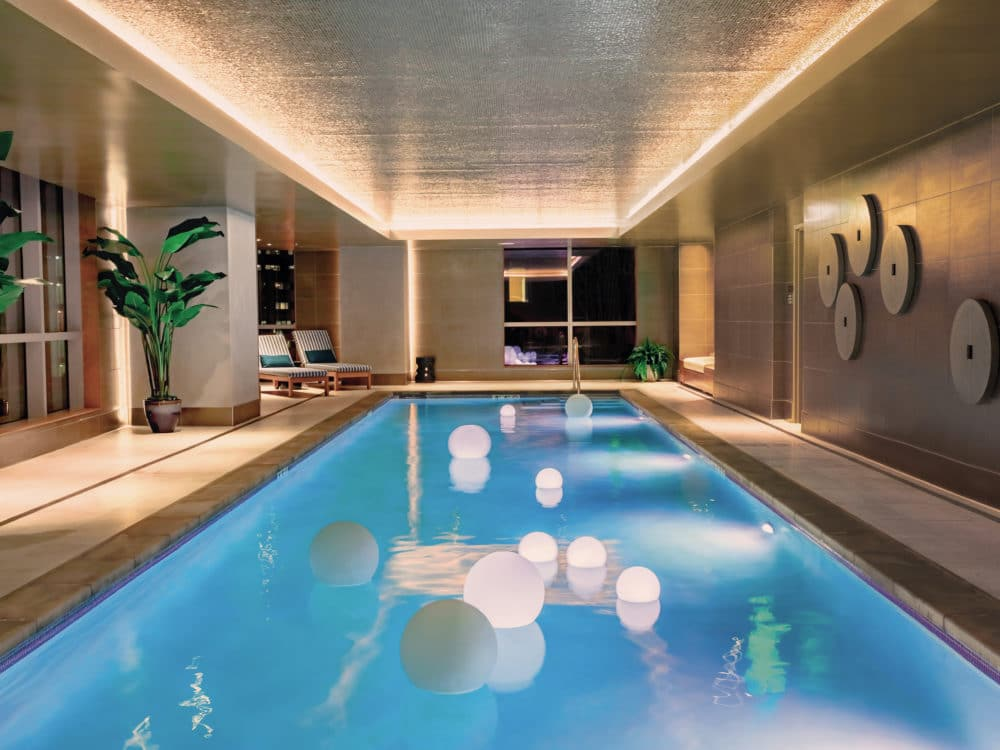 Indoor lap pool at The Avery condos in San Francisco. Bronze walls and tan floor with lounge chairs and access to showers.