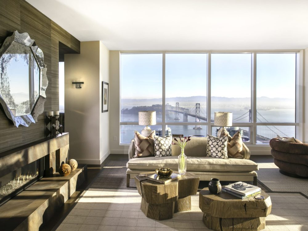 Penthouse living room at The Avery condos in SF. Open living space and floor-to-ceiling windows with views of the Bay Bridge.