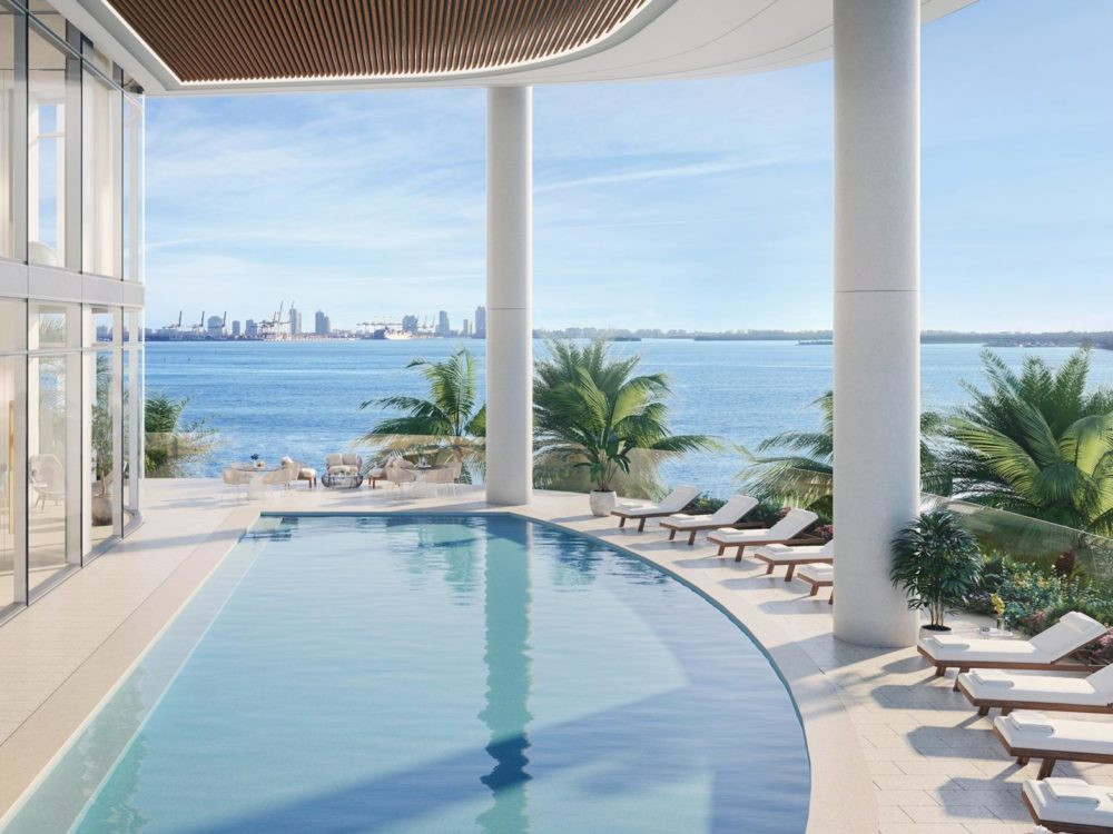 Bayfront pool at Una Residences in Miami. Large outdoor covered pool with beach chairs, planters, and a view of the marina.