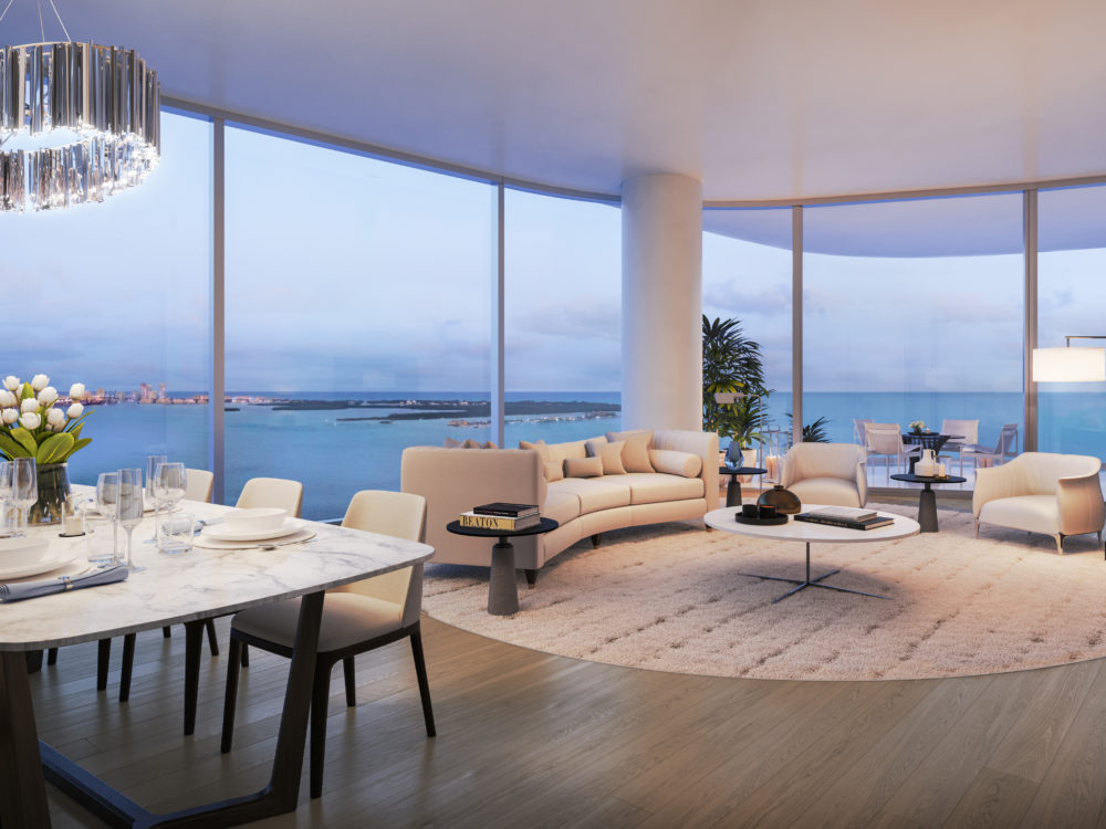 Condo living room at Una Residences in Miami. Open room with dining table, a couch, coffee table, and clear views of the bay.
