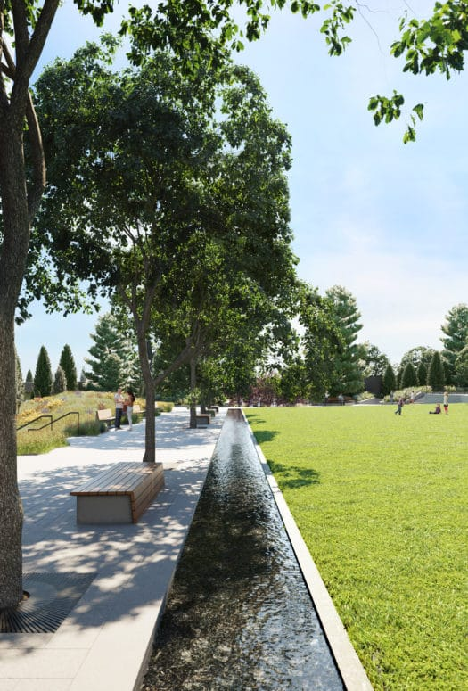 Lawn and park between the tower of Waterline Square in New York. Cement walkway with trees and benches border the lawn.