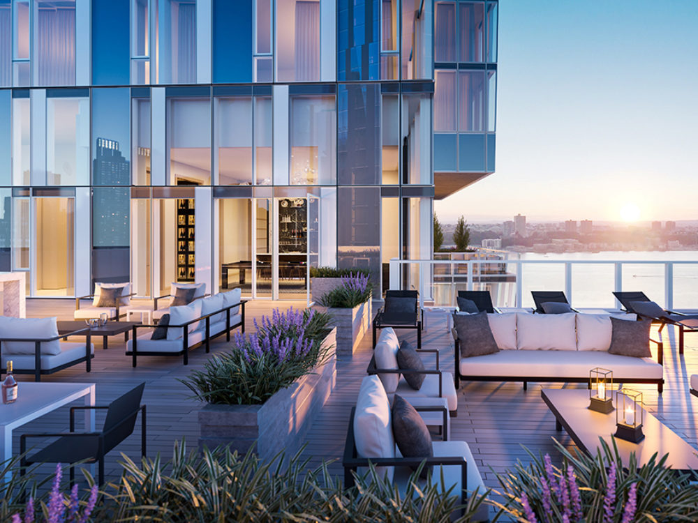 Exterior view of Waterline Square condominiums rooftop terrace. Includes skyline view of NYC and lounging furniture.
