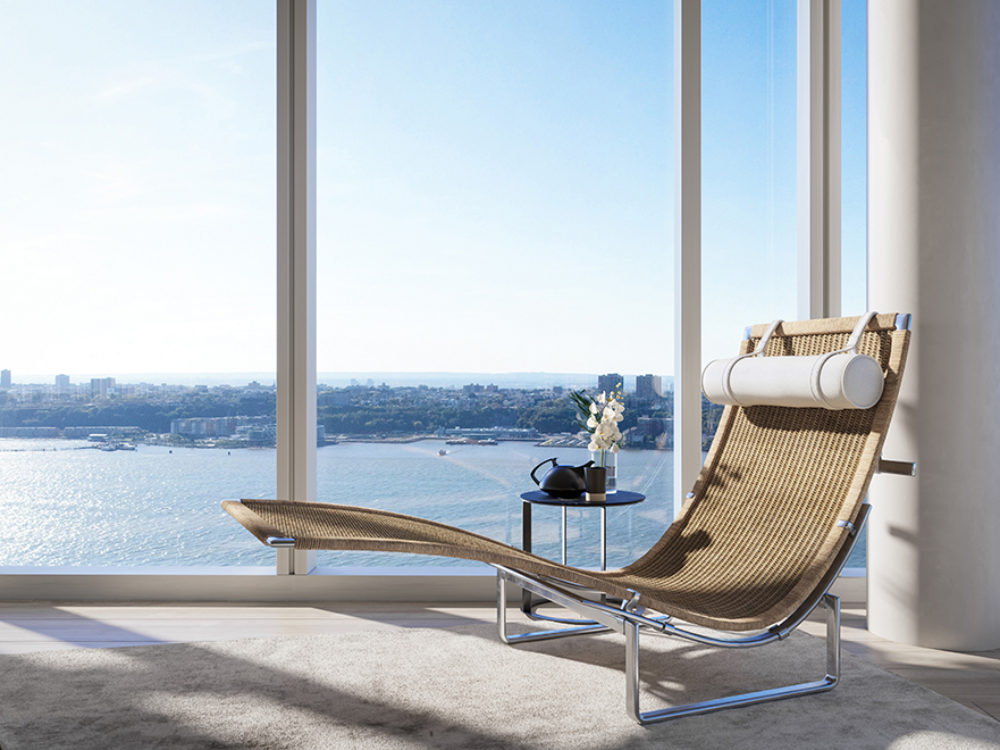 View from luxury condo at Waterline Square in New York. A lawn chair next to large window with a view of the Hudson River.
