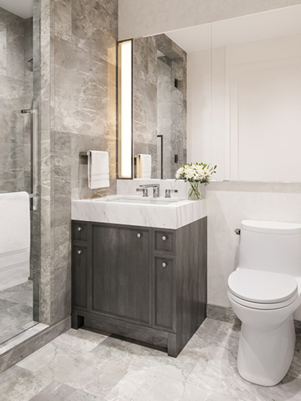 Guest bathroom at Waterline Square in NYC with toilet, single vanity, large mirror and standing shower with glass door.