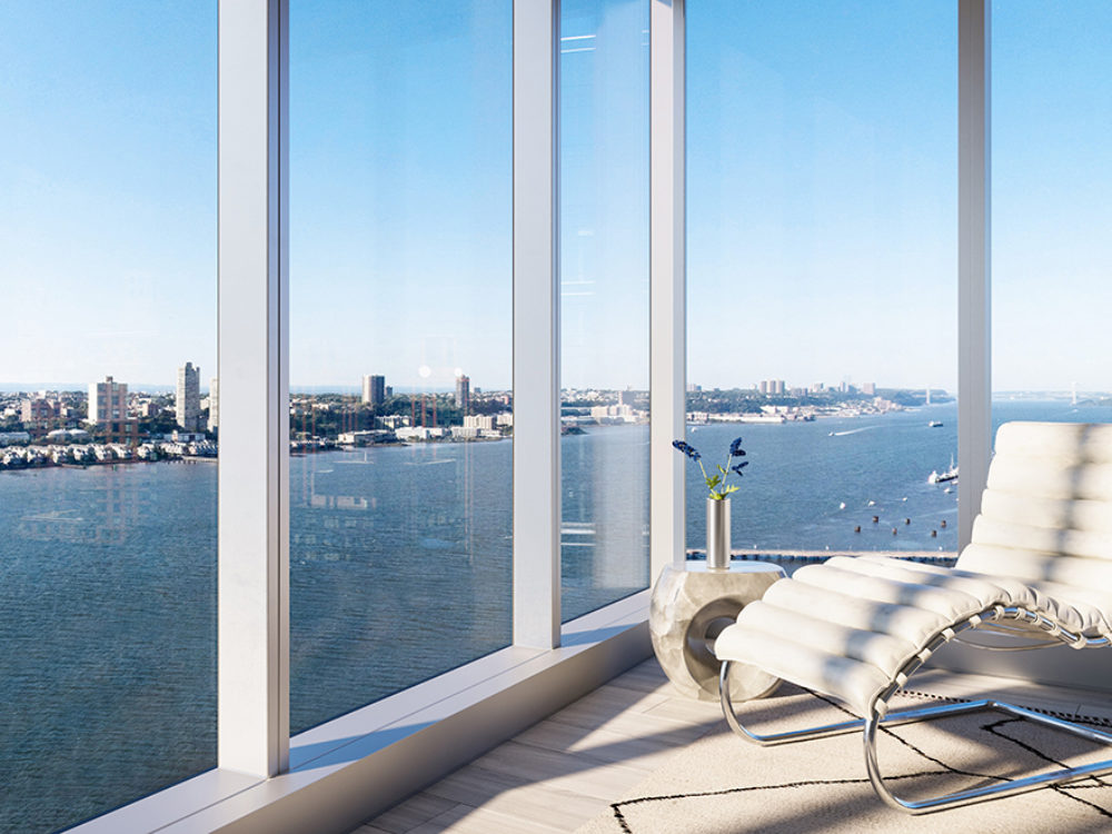 View of the Hudson River and New York City from Waterline Square luxury condo. A white lounge chair near two large windows.