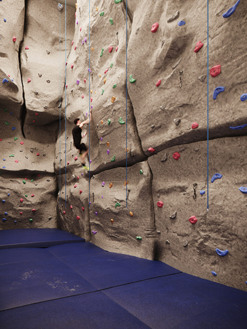 Private climbing wall with multiple safety lines and padded flooring in the Waterline Square residences in New York City.