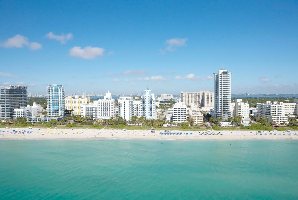 Aerial view of beach shoreline in Miami. Buildings and high rises line the shoreline with clear ocean waters in front of them.