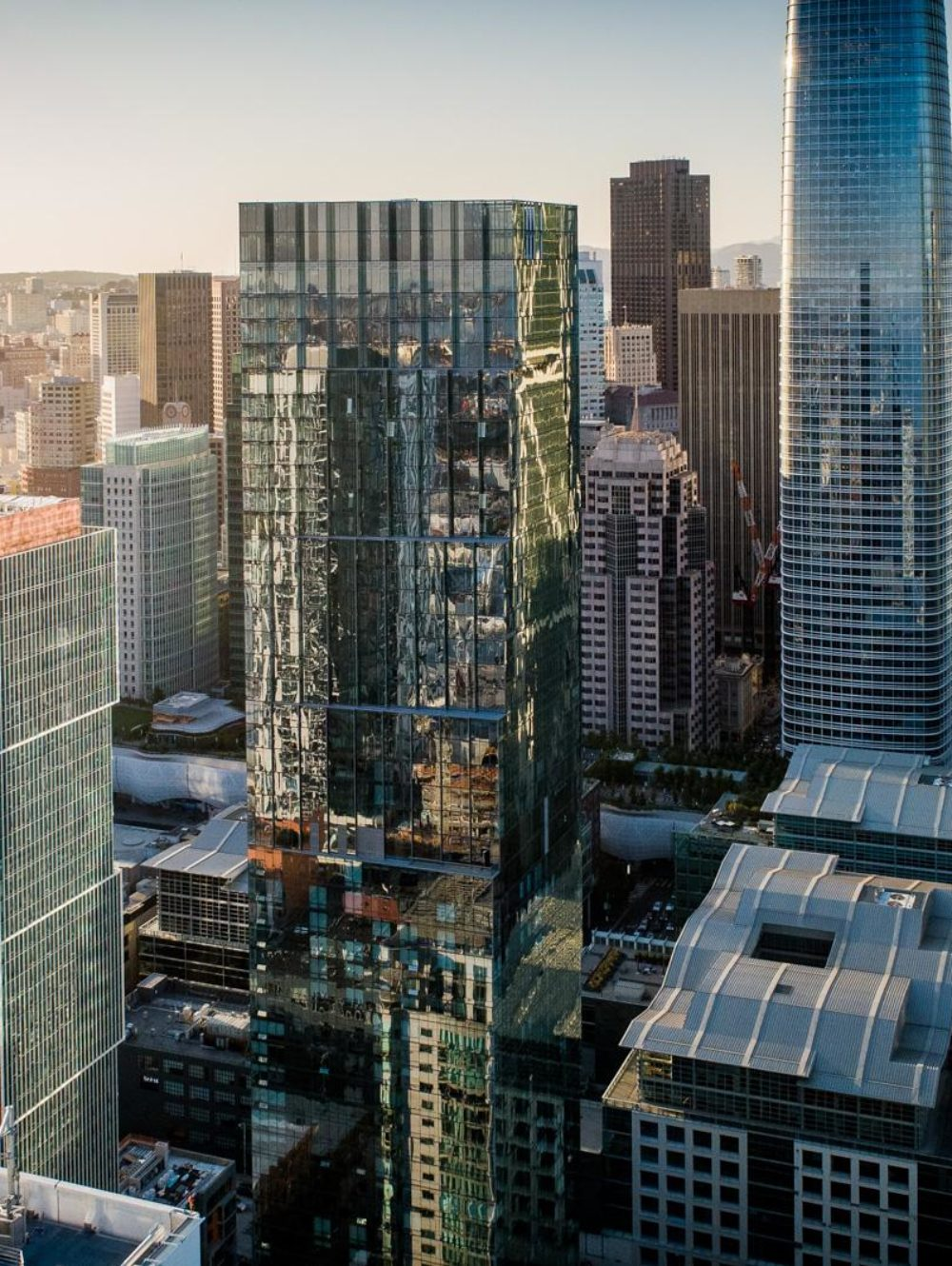 Aerial view of The Avery luxury condos in San Francisco. City skyline during sunset with The Avery glass tower in the center.