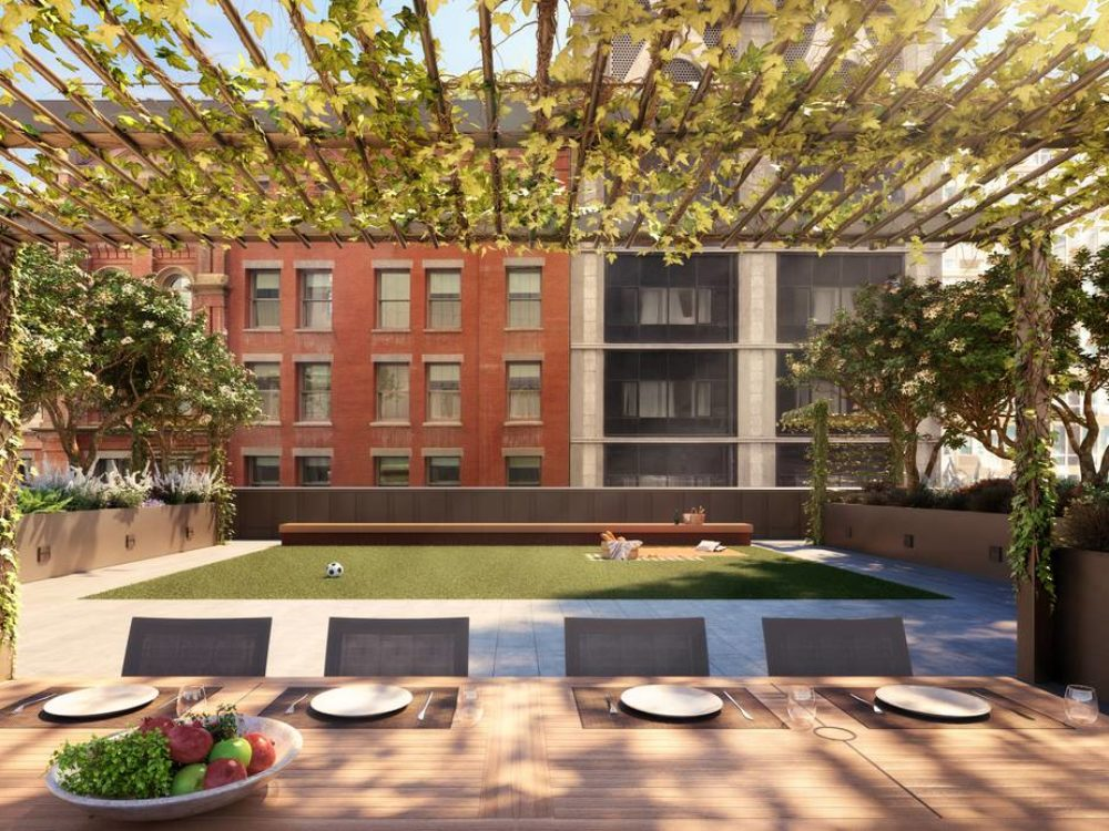 View of exterior courtyard lawn dining area in 25 Park Row condominiums. Has wood and vine structure located in NYC.