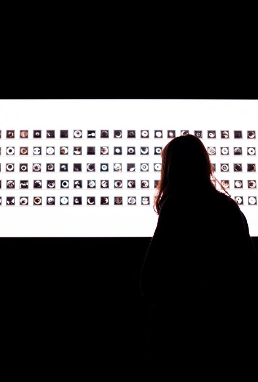 Dark room with backlit display board and shadow of woman looking at the display.