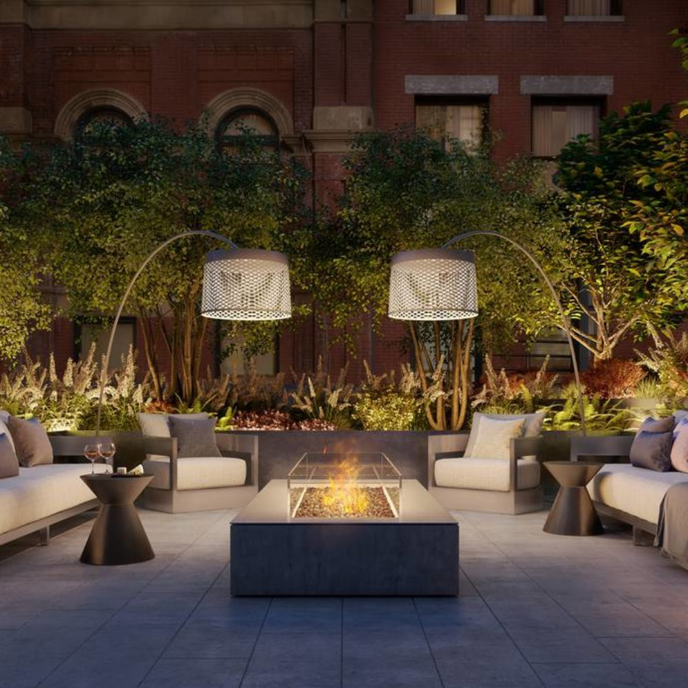 View of exterior fire pit located in 25 Park Row condominiums in NYC. Has a fireplace surrounded by beige chairs and trees.