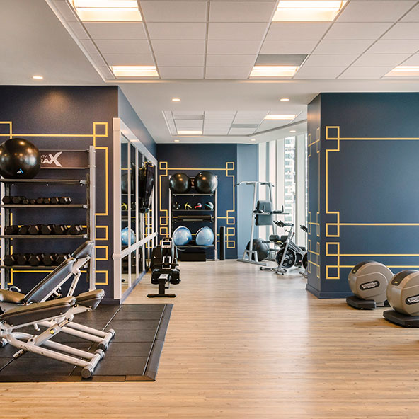 View of fitness center inside 181 Fremont condominiums located in San Francisco. Includes machines and stretching area.