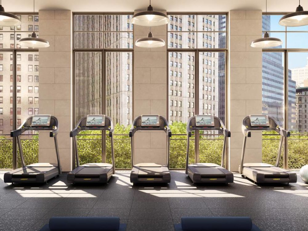 Interior view of fitness center inside 25 Park Row condominiums with cardio machines facing window view of New York City.