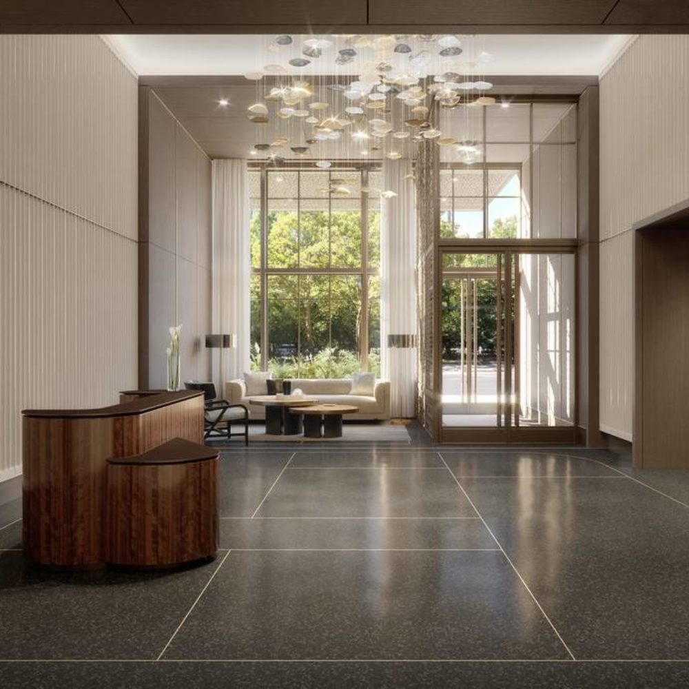 Interior view of 25 Park Row residence lobby in New York City. Includes glass windows, brown furniture, and white walls.