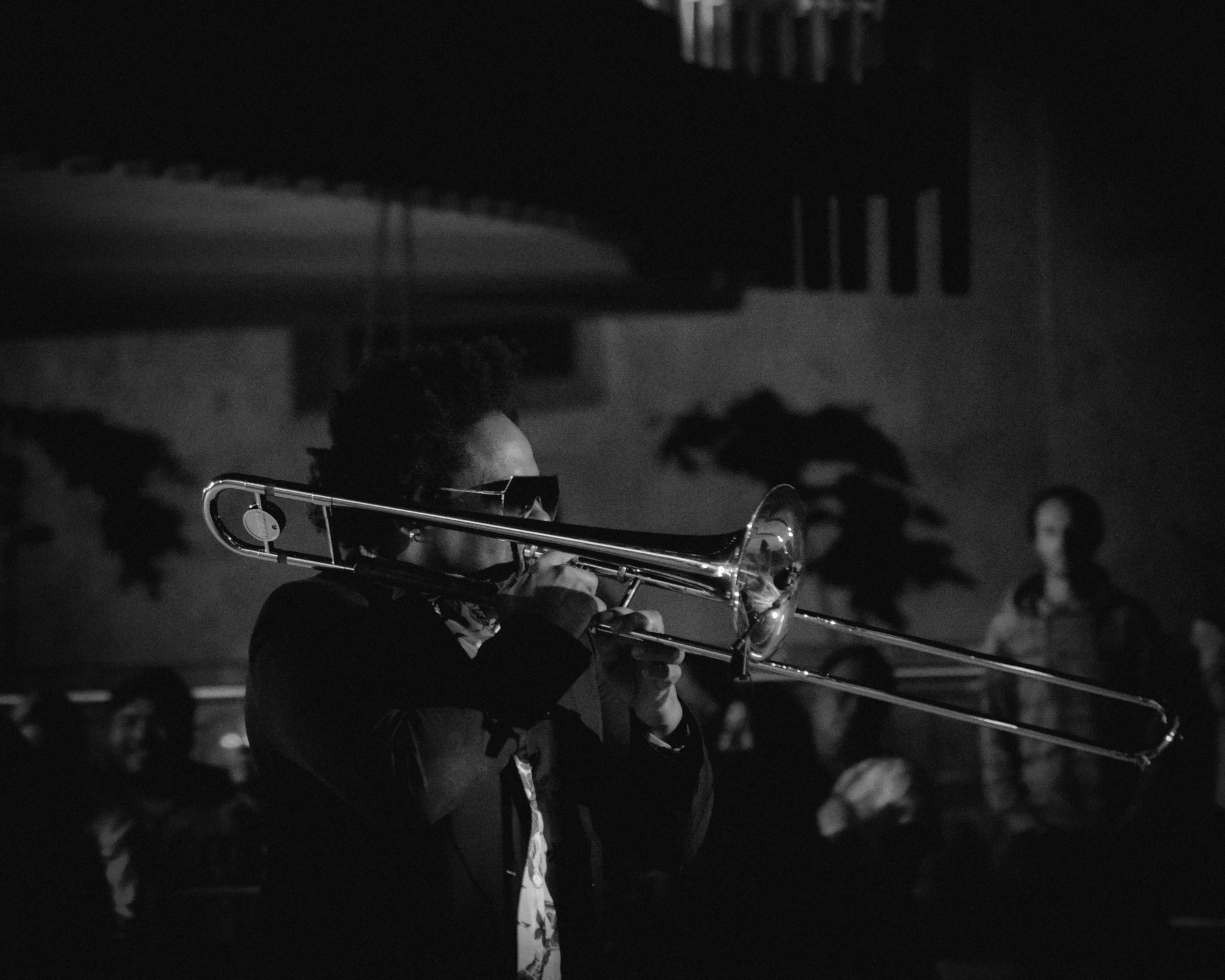 Black and white photo of musician playing the trombone. Side profile of the performer and audience members in the background.