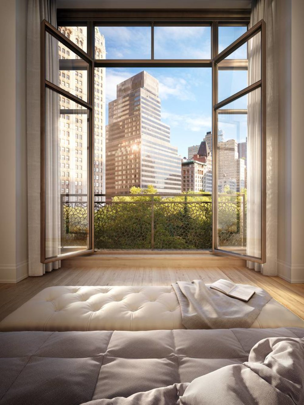 Interior view of Juliet balcony of 25 Park Row residences with view of NYC. Includes a brown and beige sofa with pillows.