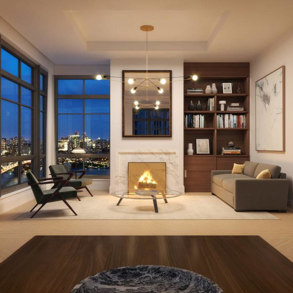 Interior view of living room with fireplace in 25 Park Row with skyline view of New York City. Has white walls and furniture.