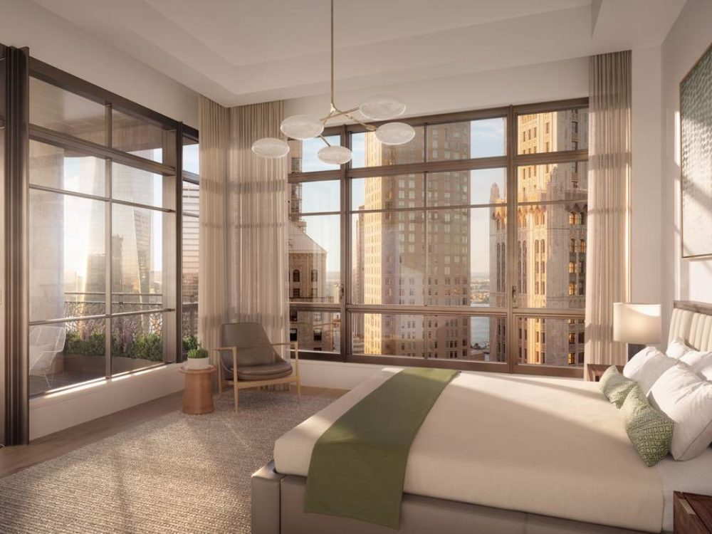 Interior view of 25 Park Row residence master bedroom. Includes view of NYC, private terrace, and light colored walls.