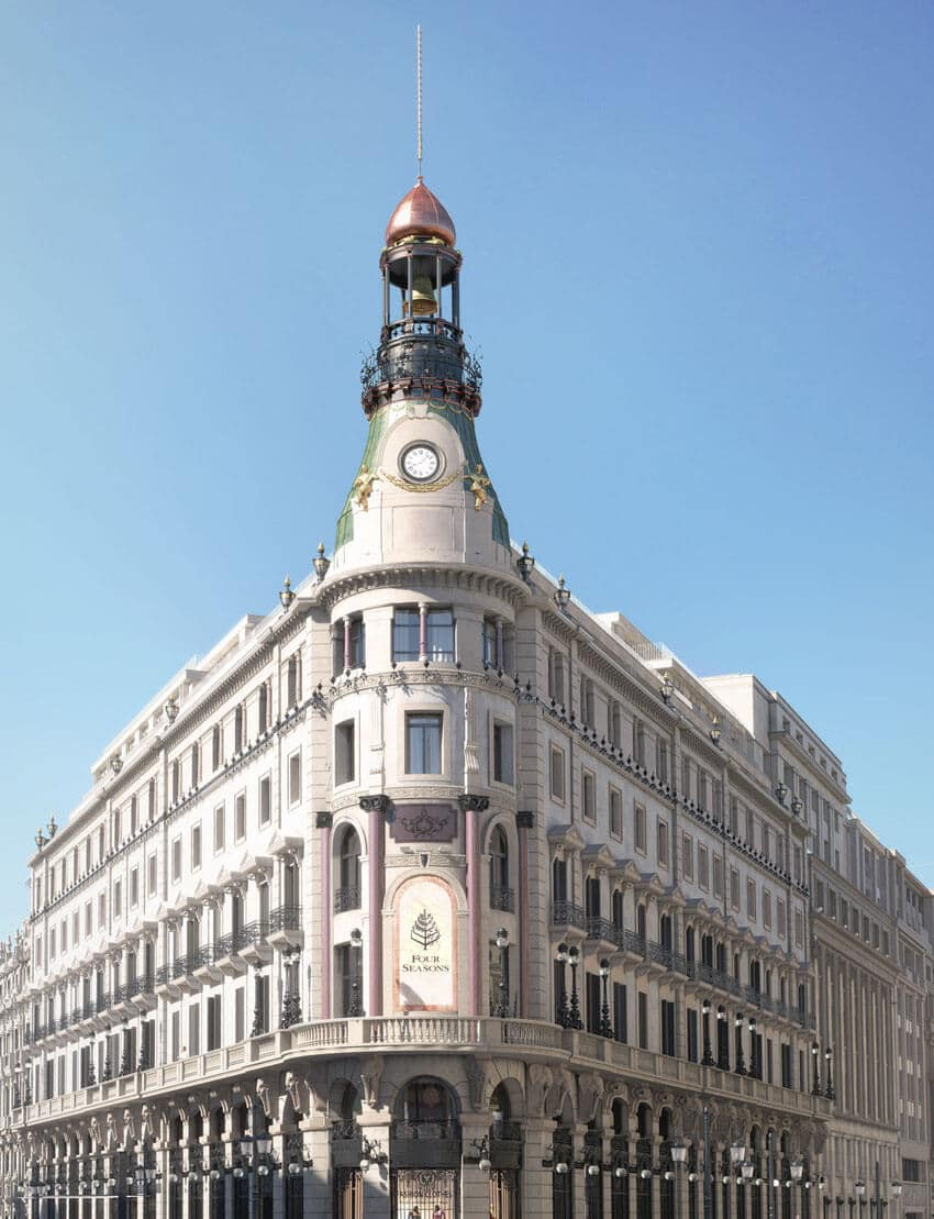 Exterior view of the Four Seasons Hotel at Canalejas in Madrid. White stone building with columns bordering the building.