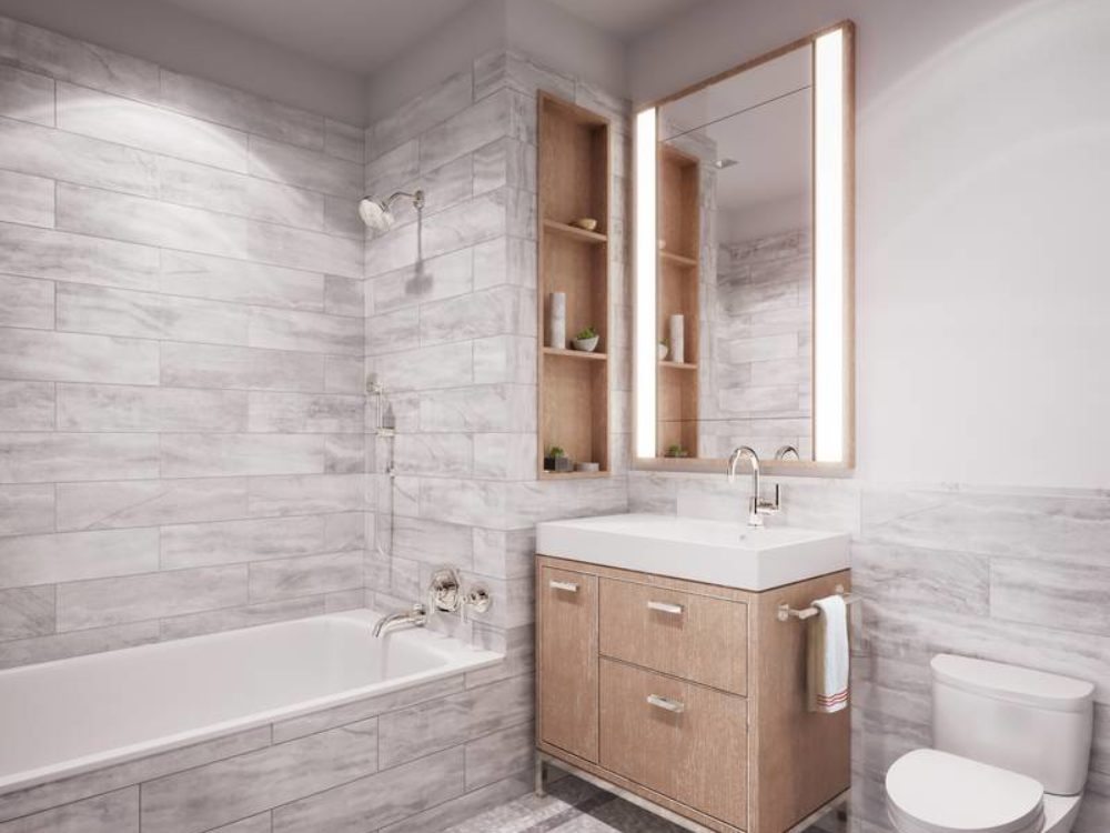 Interior view of 25 Park Row residence secondary bathroom with grey panelling and white walls located in New York City.