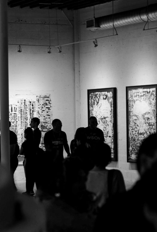 Black and white photo by Ruben Ramirez of a crowd at the Art Basel festival with three pictures and a mural on the far walls.