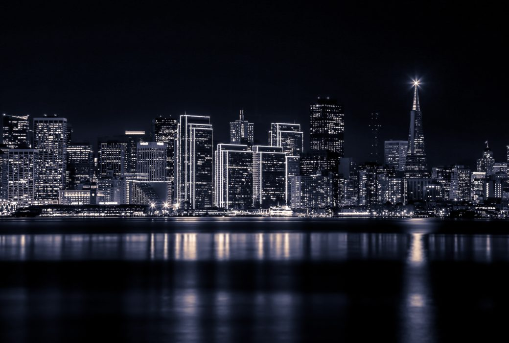 Black and white photo of San Francisco skyline at night. High rises on the bay with their images reflecting in the water.