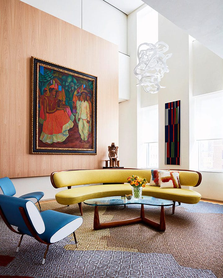 Interior living space of Park Avenue Triplex designed by Amy Lau. High ceilings, a brown accent wall, and two couches.