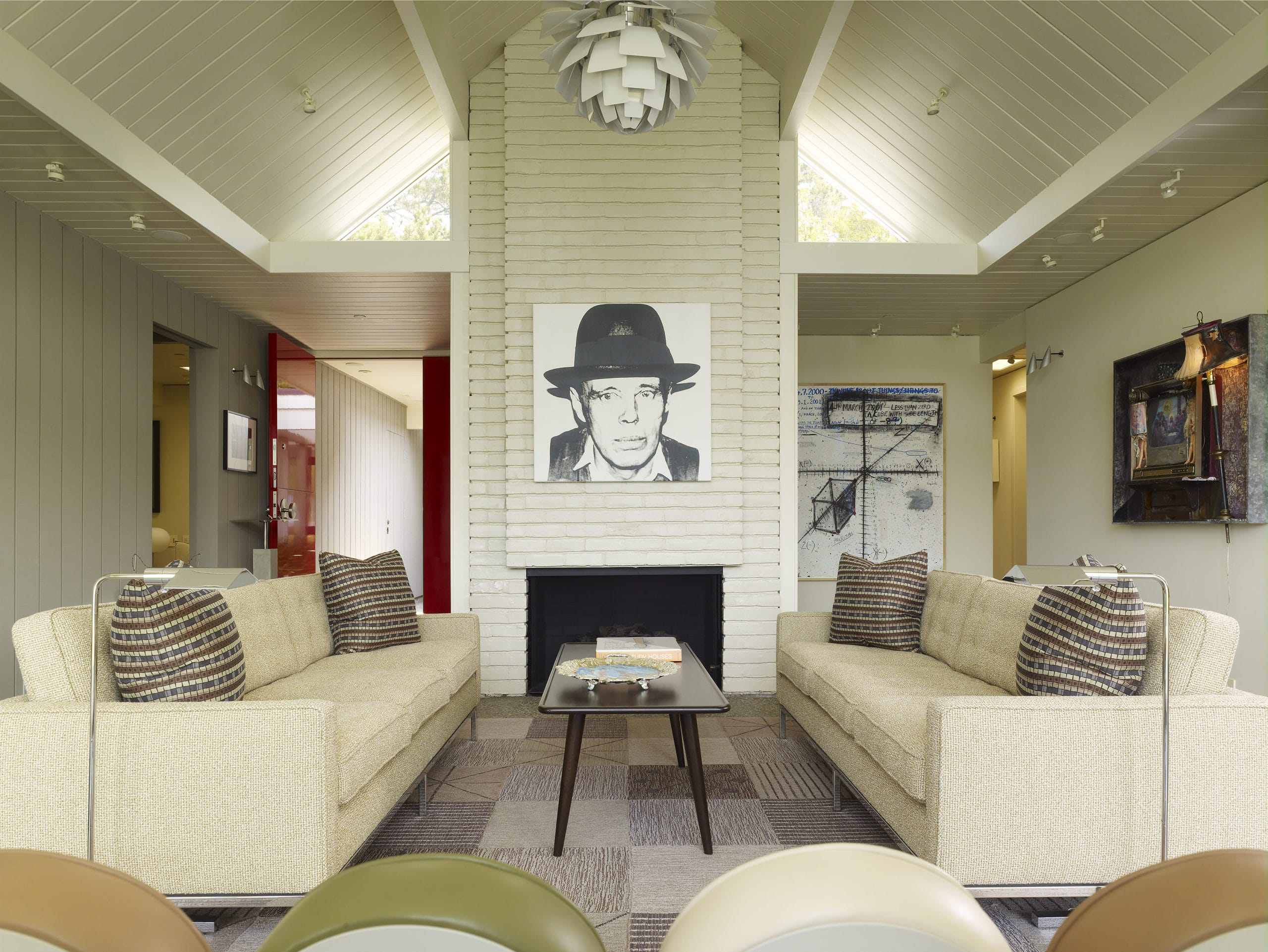 Living room with gray-stained wood walls, a brick fire place with a black and white picture hanging and two couches.