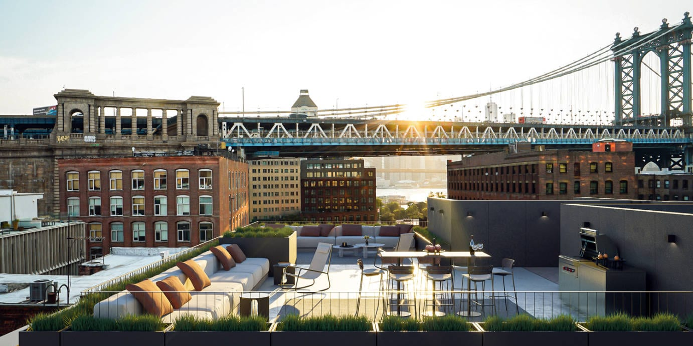 Rooftop patio at 168 Plymouth luxury condos in New York. Multiple seating areas, a bbq, and city views during sunrise