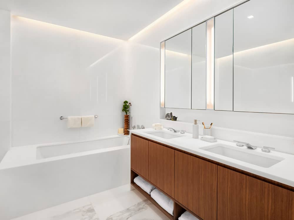 Bathroom in The Hayworth luxury condos, New York. White stone throughout with double vanity, large mirror and full tub.