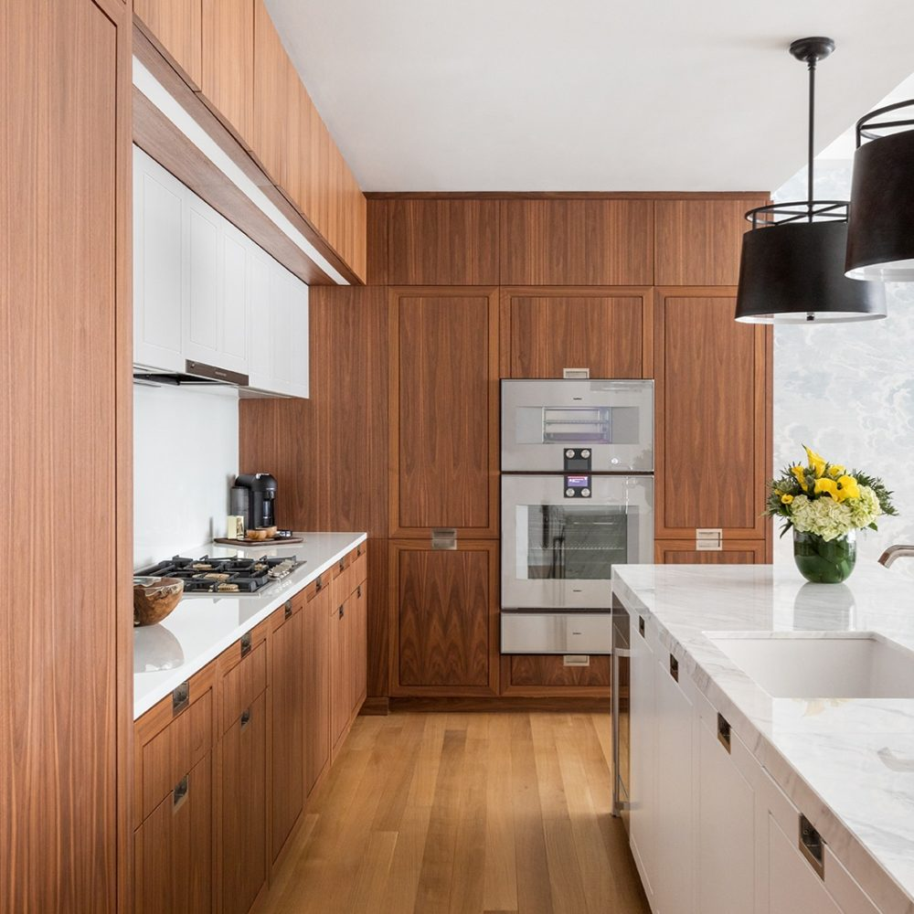 Kitchen in The Hayworth condominiums, NYC. Walnut cabinets with white stone countertops, range hood and center island.