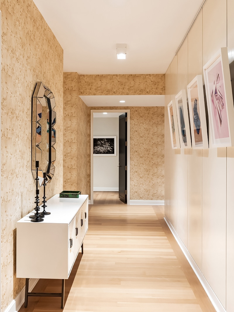 Hallway in The Hayworth luxury condominiums in NYC. Tan wallpapered hallway with a dresser, hanging mirror and paintings.