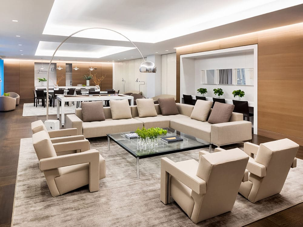 Community lounge at The Hayworth condominiums in New York. Communal room with a tan couch & chairs and a large dining table.