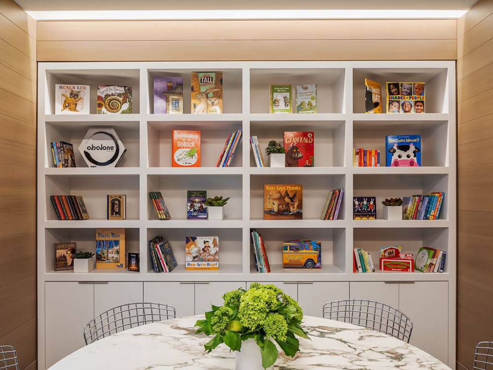 Children's play area at The Hayworth in NYC. White shelving unit with children's books and games and a small round table.