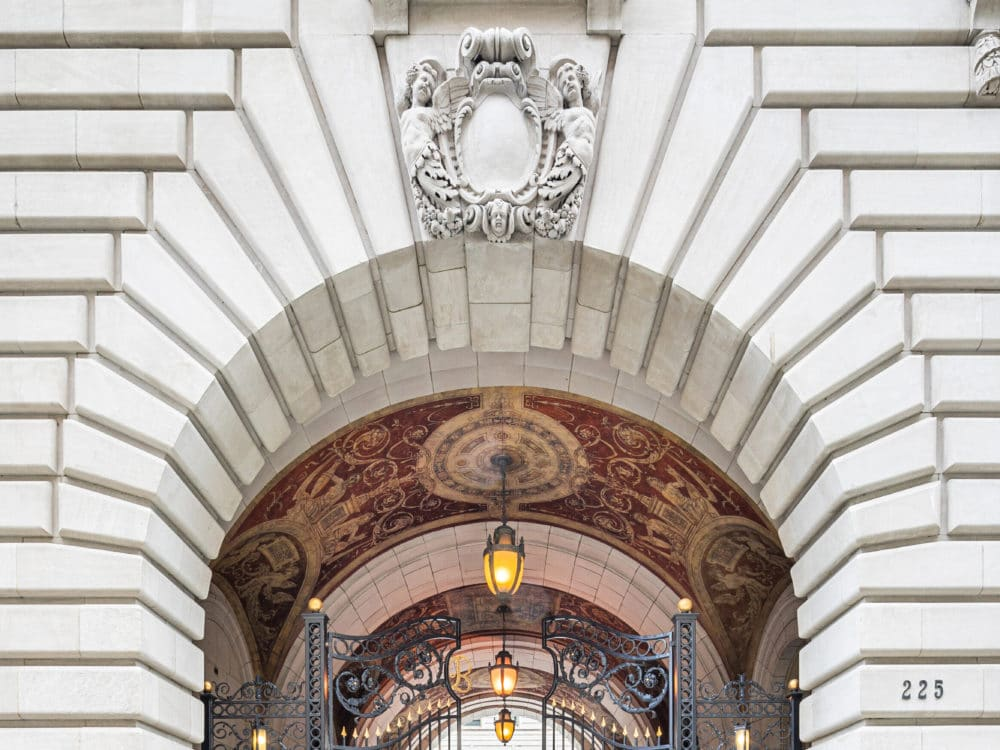 The courtyard entrance at The Belnord in NYC. Two story limestone archway with large iron gates opening into the courtyard.