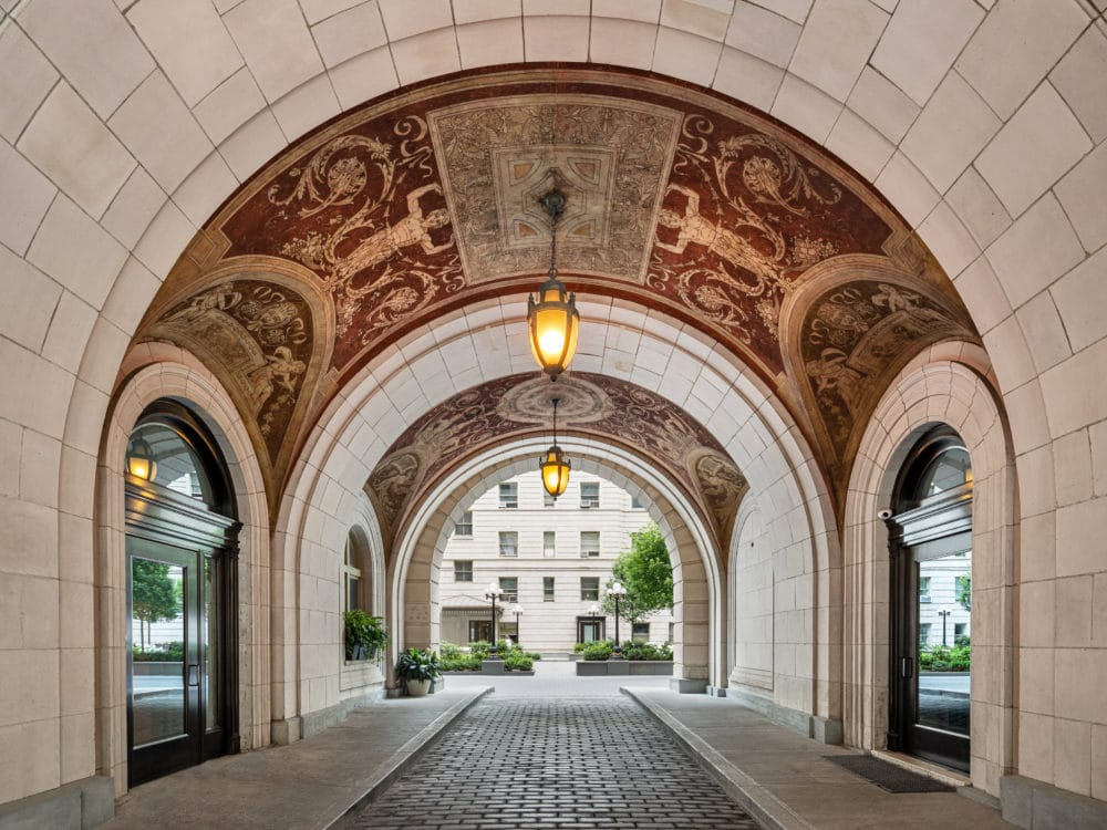 View of the archway interior at The Belnord Apartments in New York. Light gray limestone and two hanging lights.