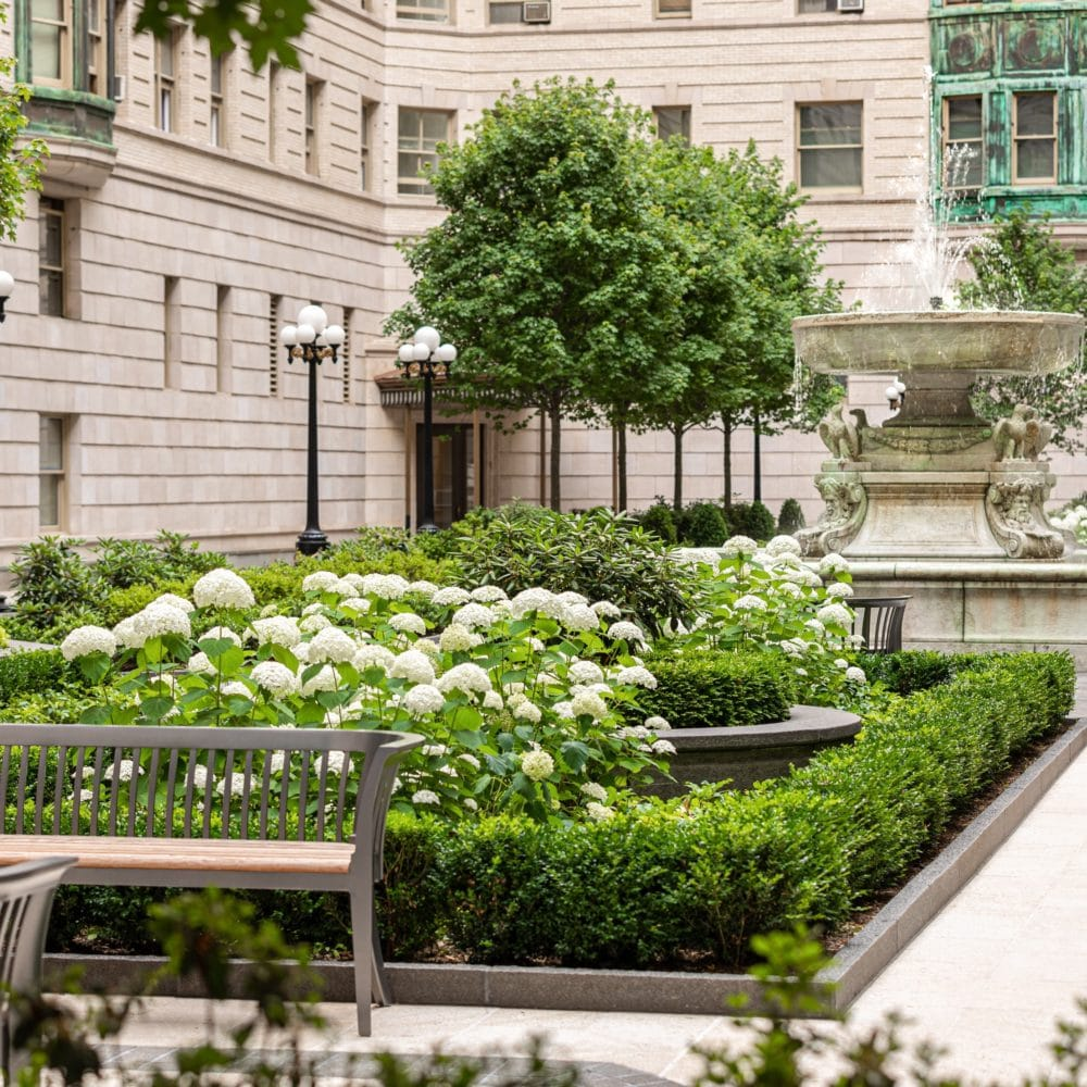 Close up of the courtyard at The Belnord apartments in NYC. Benches next to center flower beds and a water fountain.