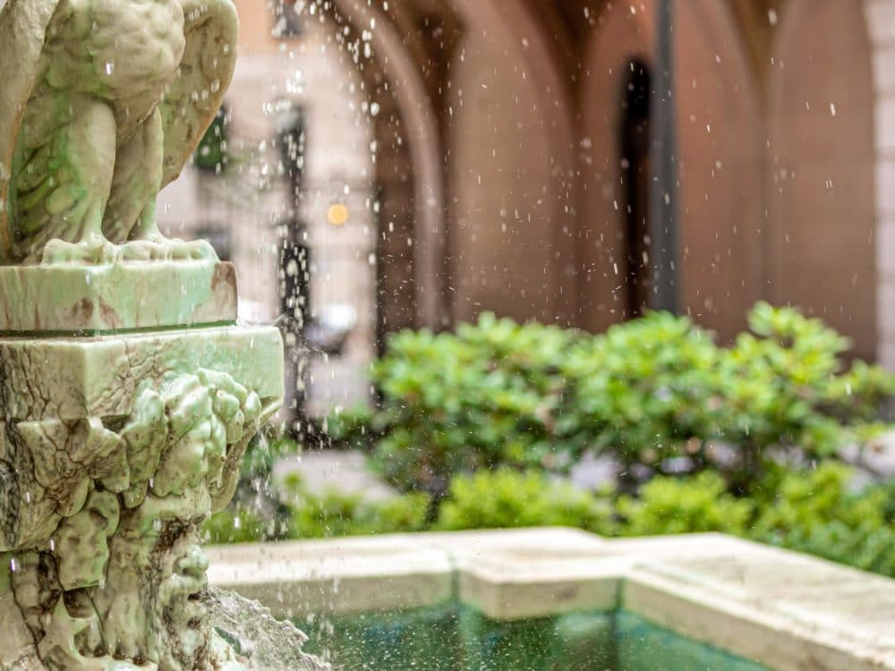 Close up of the courtyard fountain at The Belnord in NYC. Water dripping over a stone eagle with an archway in the distance.