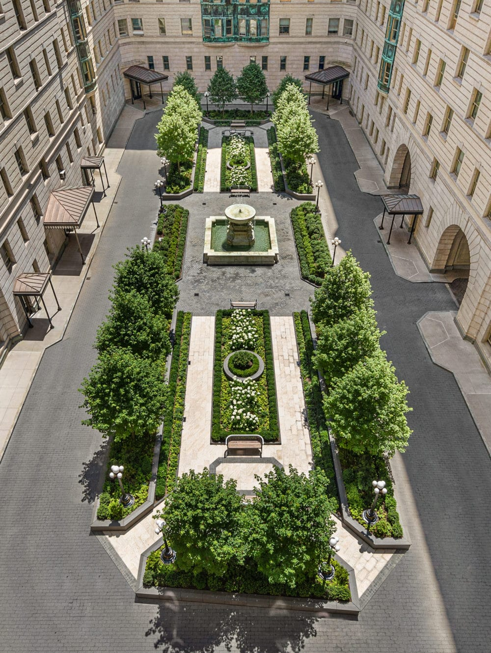 Aerial view of the courtyard at The Belnord apartments in New York. Large trees, raised planters and a water fountain.